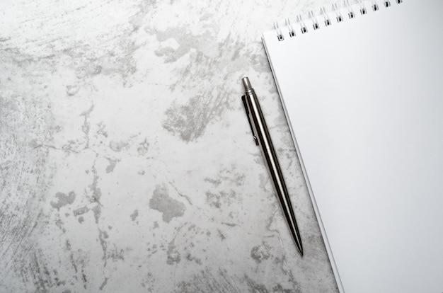 Блокнот с ручкой металла серой на каменной предпосылке.