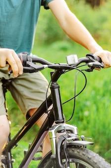 Мужчина едет на горном велосипеде по летней лесной дороге