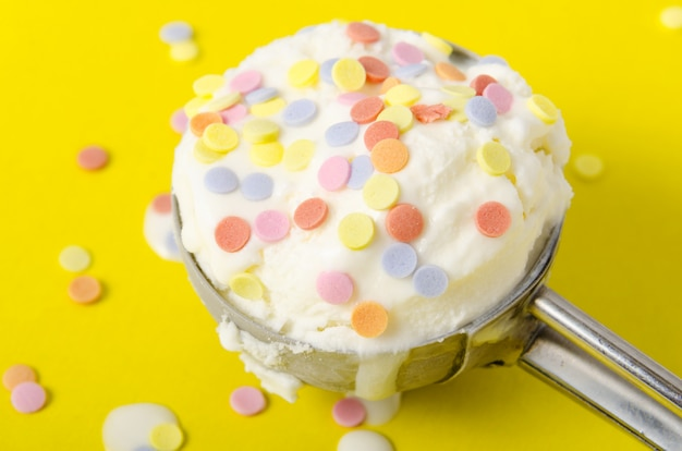色のボールで飾られた金属のスプーンの黄色の背景にバニラアイスクリーム。閉じる