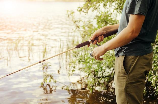 Мужчина в футболке и темных штанах ловит рыбу на озере с белой удочкой на фоне кустов и травы. концепция активного отдыха.