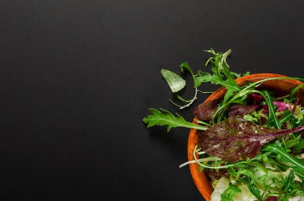 ルッコラと黒の背景上にボウルにレタスのグリーンサラダ。