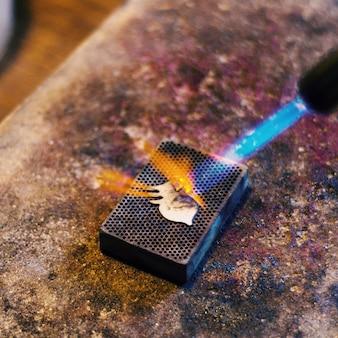 ガスバーナーで石の上に宝石類の詳細を燃やす。手作りのホームワークショップ。