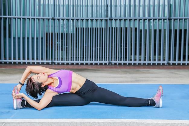 若くて健康的なアジアの女性は公共の公園で彼女の体を伸ばしています