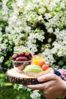 ミックスフルーツとオレンジジュースのセットをボウルに多くのナツメヤシを示すラマダンのインスピレーション