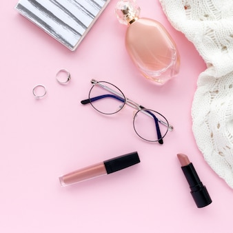 白いセーター、メガネ、メモ帳、女性用化粧品、ピンクのパステル調の背景にアクセサリー