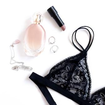 Стильное черное кружевное белье, флакон духов, косметика и аксессуары на белом фоне