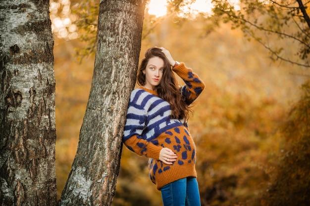 秋の散歩にセーターで妊娠中の女性