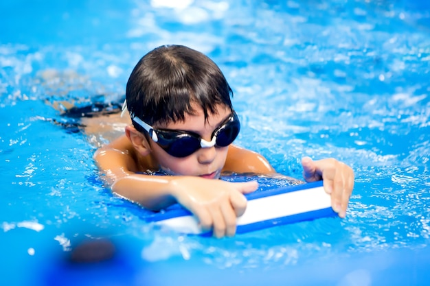 小さな男の子はプールで泳ぐために訓練します