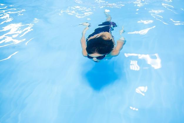 プールで泳ぐことを学ぶ少年