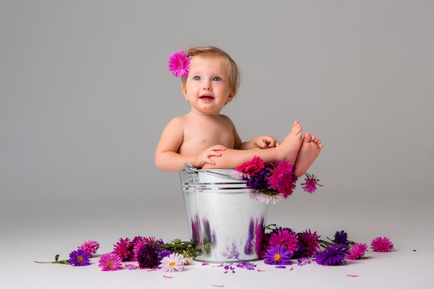花のバケツに座っている女の赤ちゃん