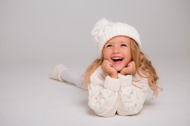 ニットの白い冬の帽子で少し縮れ毛の少女の肖像画