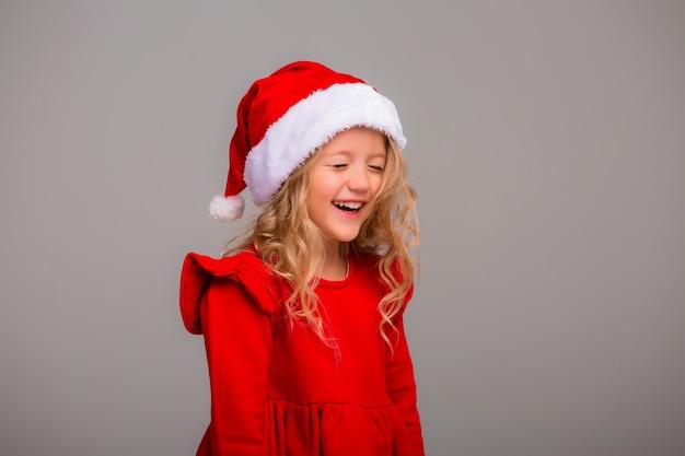 Маленькая девочка блондинка улыбается в шляпу санта на