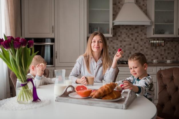 Мама с детьми завтракает на кухне