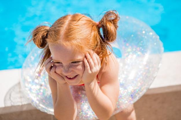 プールで水泳サークルを持つ少女
