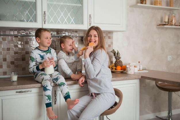 キッチンで朝食を食べている子供を持つ母