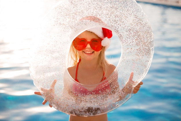 Маленькая девочка в новогодней шапке летом в бассейне