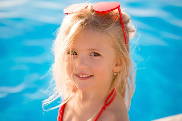 Маленькая блондинка в бассейне летом