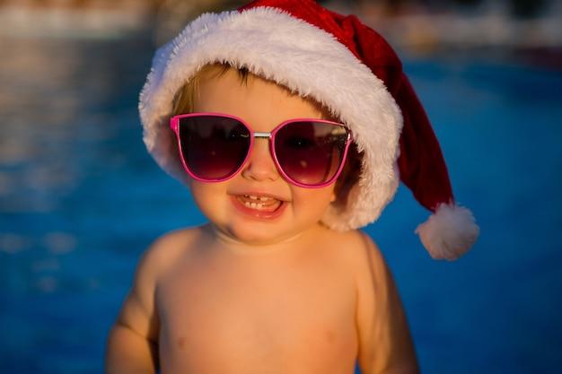 Ребенок в шапке санты и солнцезащитные очки в бассейне