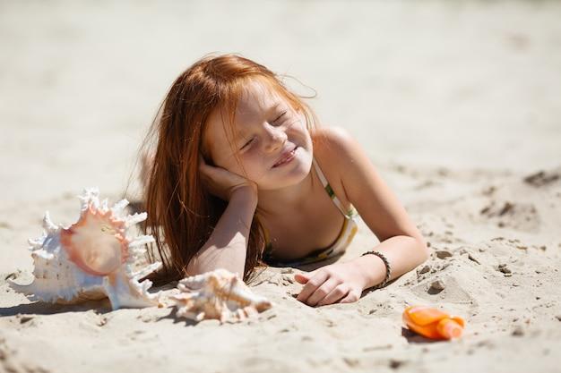 Маленькая рыжая девочка лежит на песке, загорает