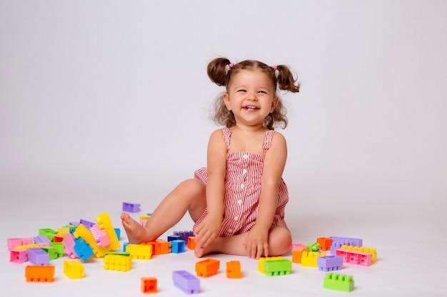 Девочка играет с разноцветным конструктором