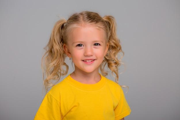 Маленькая блондинка улыбается на светлом фоне