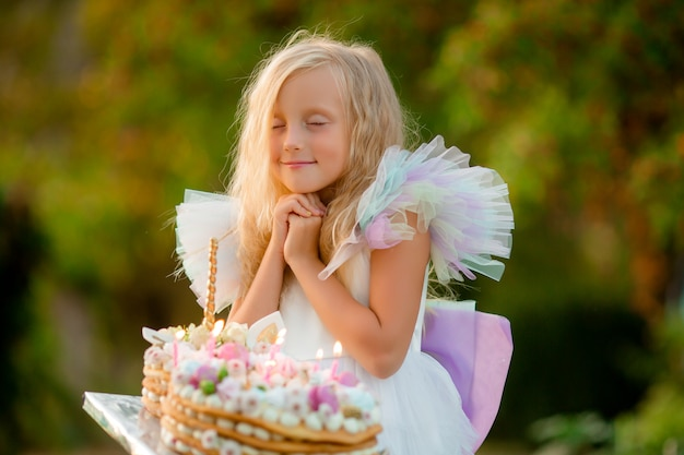 小さな女の子が願い事をして、ケーキのろうそくを吹き消す