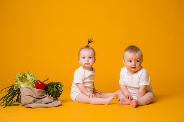 Два мальчика и девочка в окружении свежих овощей в эко сумке на оранжевом