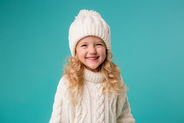 冬の白い帽子とセーターに笑みを浮かべて、スケートを保持している少女