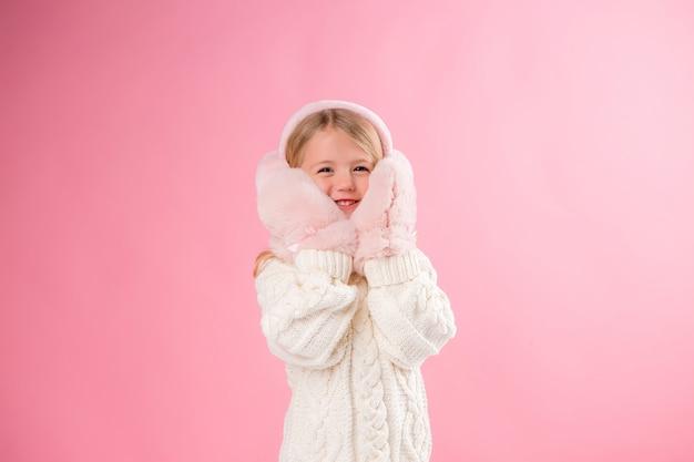 Маленькая девочка в розовых варежках и наушниках на розовой стене