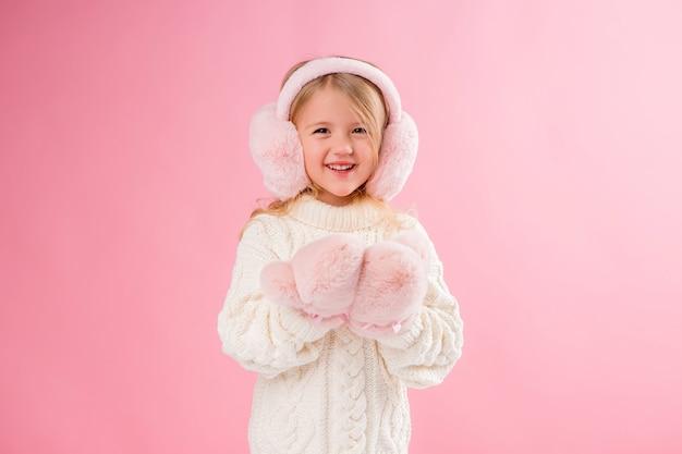 ピンクのミトンとピンクの壁にヘッドフォンの少女
