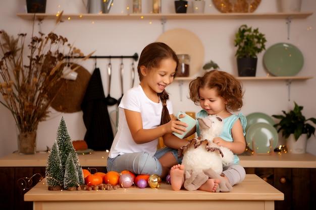 Две девочки едят мандарины в рождественской кухне