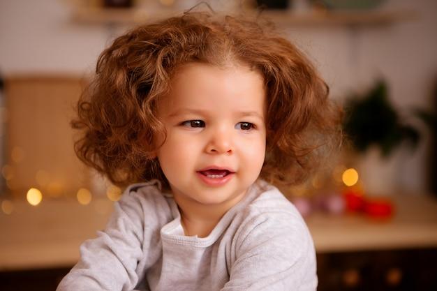テーブルの上のクリスマスキッチンに座っている女の赤ちゃん