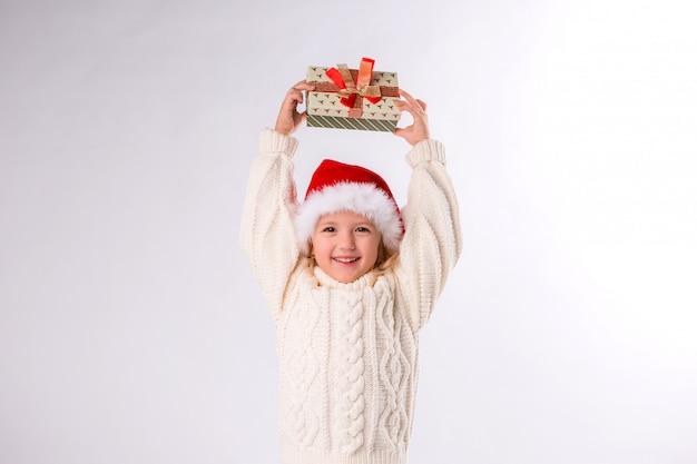Девочка улыбается в новогодней шапке с подарочной коробкой на белом фоне