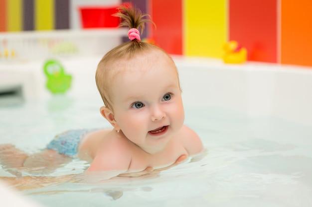 赤ちゃんは水泳、幼児水泳、赤ちゃんのプールを教える健康的な家族の母親を学ぶ
