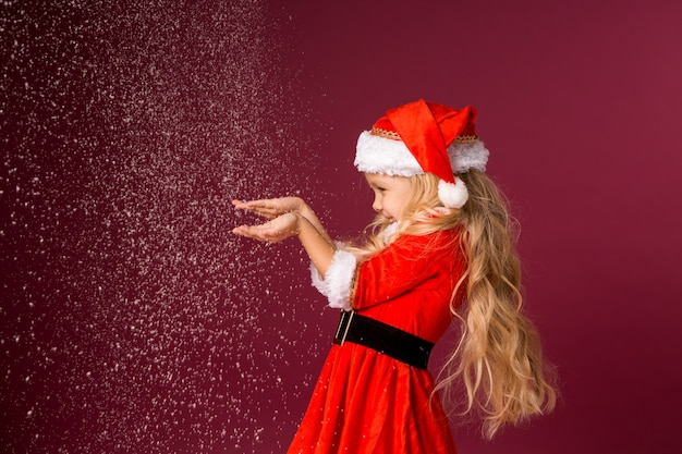 サンタのスーツで金髪少女は彼女の手から雪を吹く