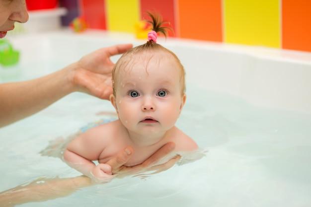 Ребенок учиться плаванию, детское плавание, здоровая семья мама обучает ребенка плаванию