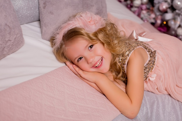 クリスマスツリーの横にあるベッドで金髪少女。クリスマス・イブ