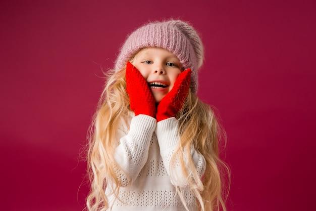 Маленькая блондинка в вязаной шапке и варежки улыбки. зимняя одежда