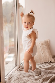 女の赤ちゃんは窓辺に立って、窓の外に見える