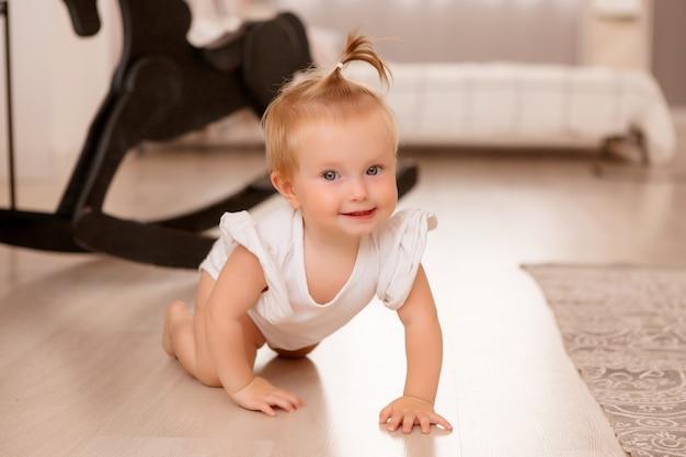 Здоровая девочка в комнате рядом с серым диваном учится ходить