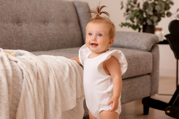 灰色のソファの隣の部屋で健康な女の赤ちゃんが歩くことを学んでいます。