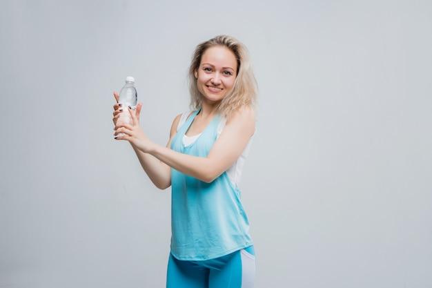 Молодая девушка в спортивной одежде с бутылкой чистой воды на белой стене