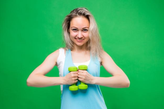 Молодая девушка в спортивной одежде держит гантели на зеленой стене, место для текста