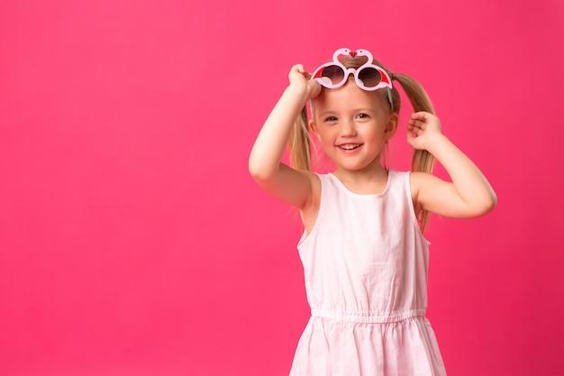 Счастливая девочка улыбается в темных очках на розовом фоне