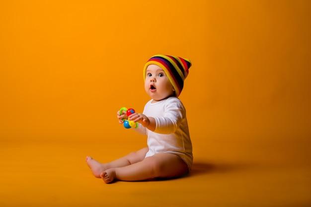オレンジ色の壁の上に座って、白いボディースーツとおもちゃを保持している色とりどりの帽子の男の子