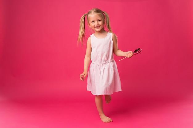 ピンクの背景にロリポップの女の赤ちゃん