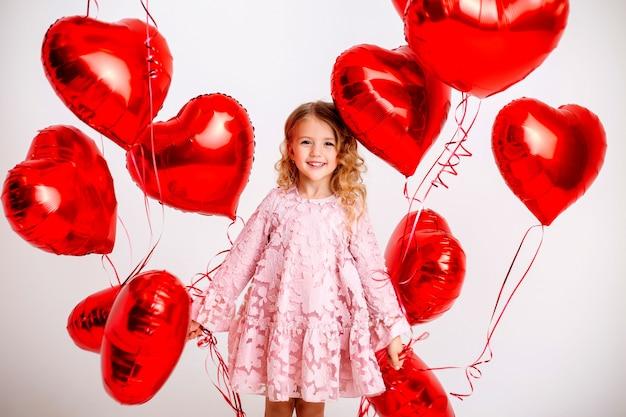 Маленькая белокурая девушка в розовом платье улыбается и держит много красных шаров в форме сердца на белой стене