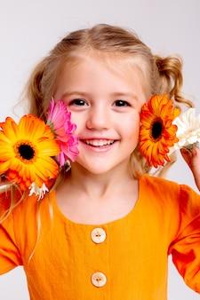 Портрет маленькой блондинки с букетом весенних цветов на светлой стене