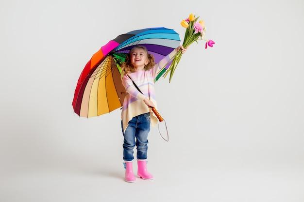 Улыбающаяся девушка в подходящей розовой рубашке и резиновых сапогах держит зонтик на белом фоне