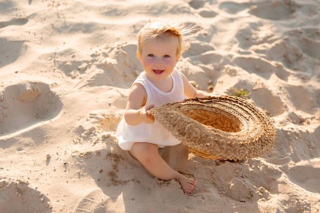 白い服と麦わら帽子の女の赤ちゃんは、夏のビーチで白い砂の上に座っています。